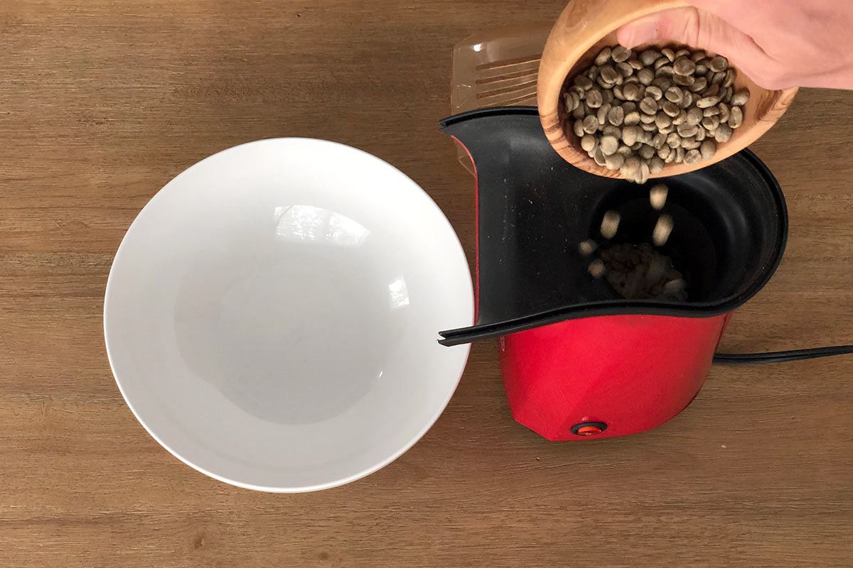 Pouring green coffee into the hot air popcorn popper for roasting
