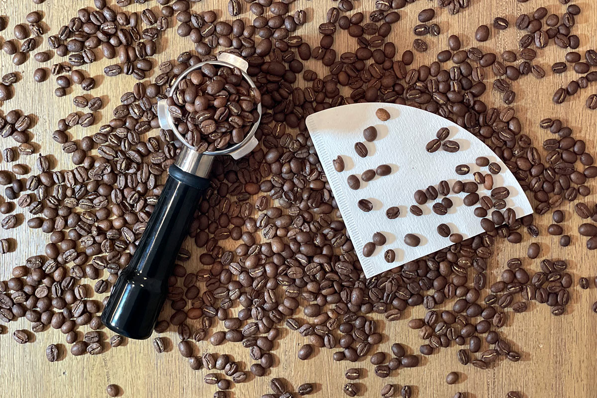 Coffee beans on table with portafilter and paper filter